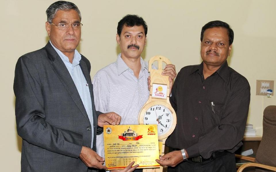 Recipient of  Government of Karnataka's 'Sakala Best Nodal Officer'  Award Sri Rajesh Shenoy, System Analyst, along with Prof. A.H. Rajasab, Vice Chancellor and Prof. D. Shivalingaiah, Registrar